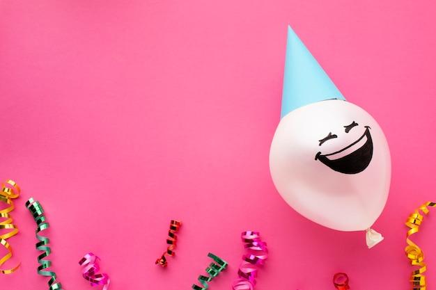 Acima da moldura com balão e chapéu de festa Foto gratuita