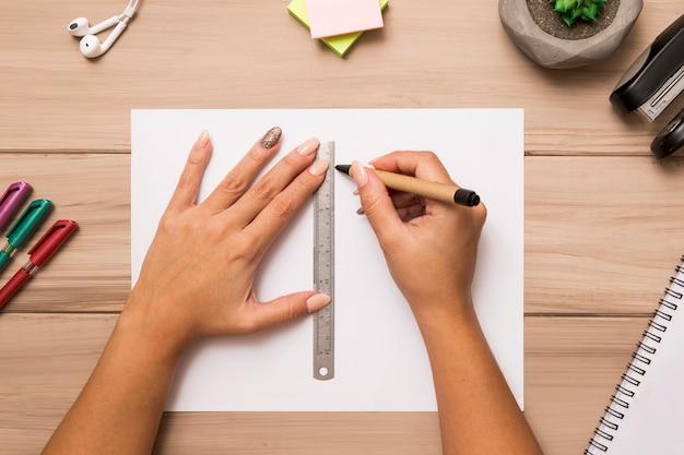 Acima de mãos femininas desenho na folha de papel com caneta e régua Foto gratuita