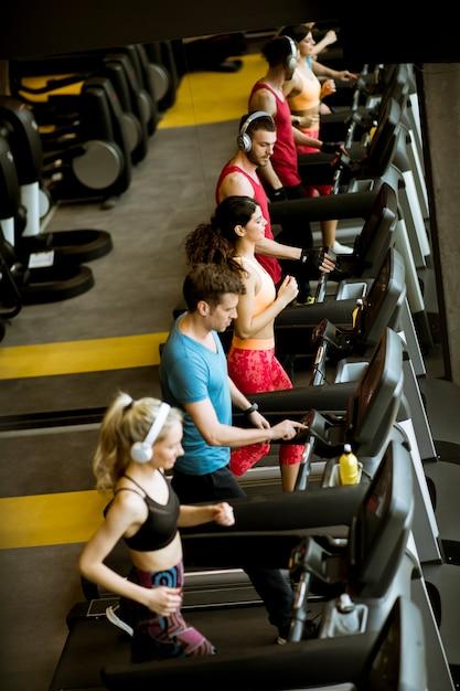 Acima vista no grupo de jovens correndo em esteiras no ginásio esporte moderno Foto Premium