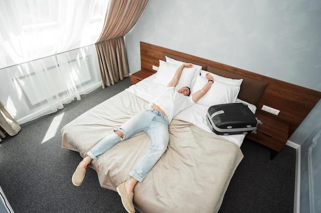 Acomodação do quarto do hotel do viajante de negócio do homem novo Foto Premium