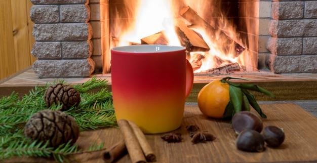 Aconchegante cena perto da lareira com caneca de bebida quente, tangarine, cones, nozes e canela sricks. Foto Premium