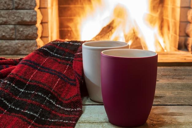 Aconchegante cena perto da lareira com canecas de chá quente e cachecol quente. Foto Premium