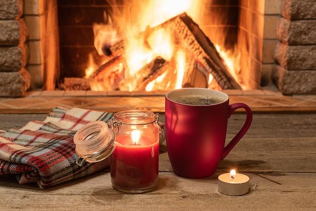 Aconchegante cena perto da lareira com uma caneca de chá quente, cachecol quente e vela. Foto Premium