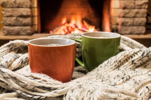 Aconchegante cena perto da lareira com xícaras de chá quente e aconchegante cachecol quente. Foto Premium