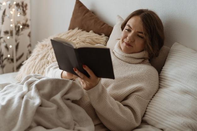 Aconchegante dia de inverno de outono. livro de leitura de mulher. estilo de vida confortável Foto Premium