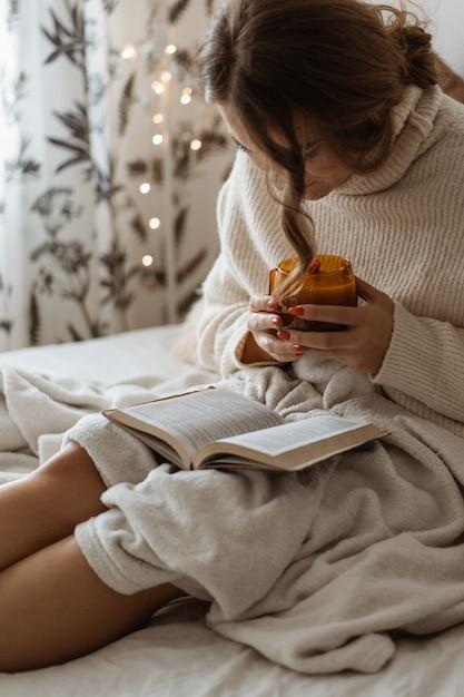 Aconchegante dia de inverno de outono. mulher bebendo chá quente e lendo o livro. estilo de vida confortável Foto Premium