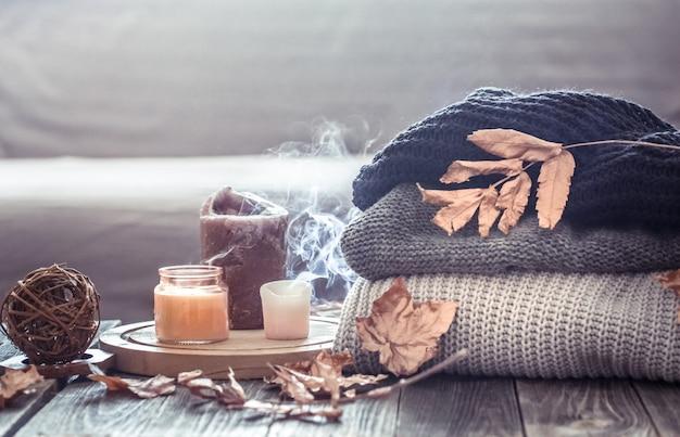 Aconchegante outono ainda vida com velas e uma camisola Foto gratuita