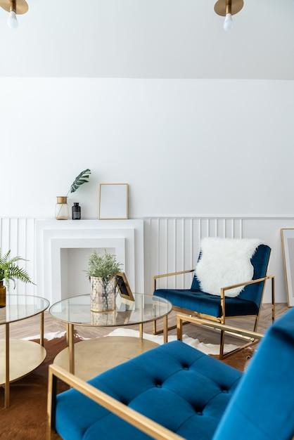 Aconchegante sala de estar com poltrona de tecido de veludo azul e dourado e mesa de centro com espelho dourado em estilo clássico moderno, com cenário de iluminação natural Foto Premium