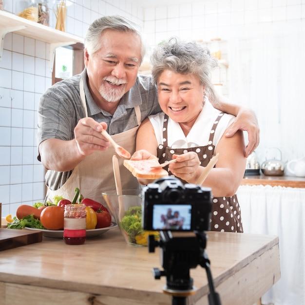 Acople a vida feliz mais idosa asiática sênior na cozinha home. avô, limpando a boca da avó depois de comer pão com geléia vlog vdo para blogueiro social. foco na câmera. estilo de vida moderno e relacionamento Foto Premium