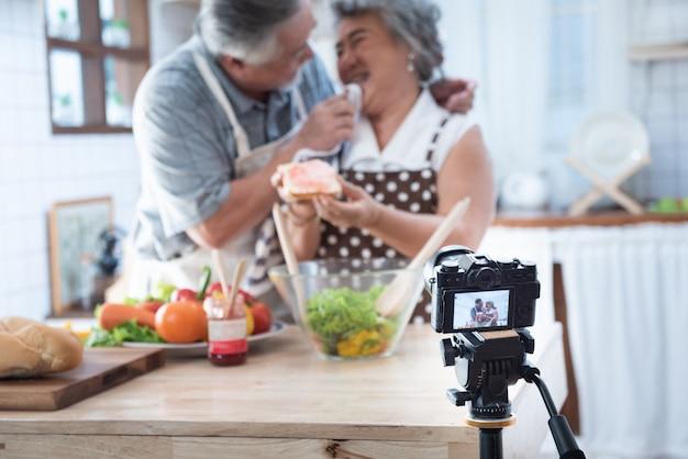 Acople a vida feliz mais idosa asiática sênior na cozinha home. avô, limpando a boca da avó depois de comer pão com geléia vlog vdo para blogueiro social. Foto Premium
