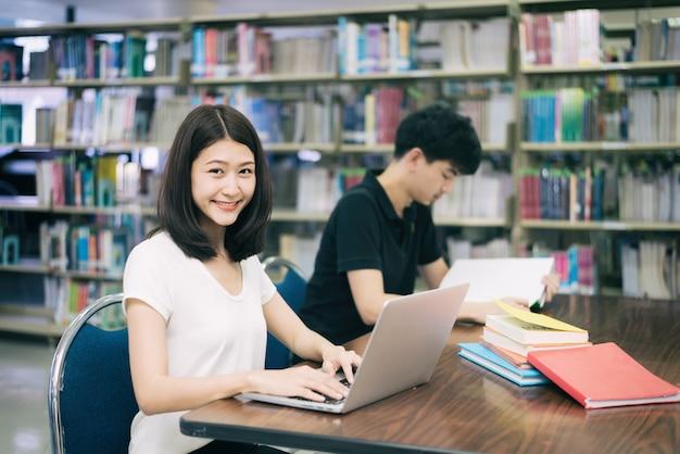 Acople estudantes asiáticos felizes com laptop e livro que falam na biblioteca na universidade. Foto Premium