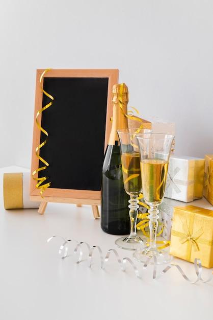 Acordo com mock-up de lousa e champanhe Foto gratuita