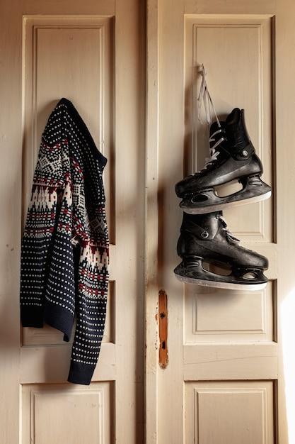 Acordo com patins de gelo e blusa pendurada na porta Foto gratuita