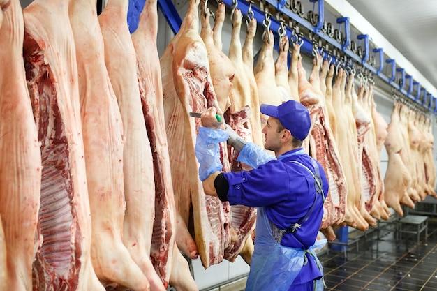 Açougueiro cortar carne de porco na fabricação de carne. Foto Premium