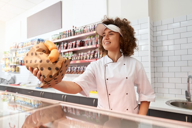 Açougueiro feminino dando salsichas no balcão. Foto gratuita