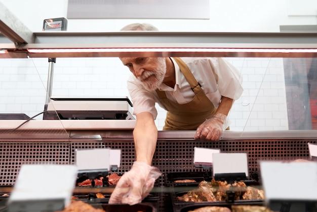 Açougueiro masculino levando carne crua fora do balcão. Foto gratuita
