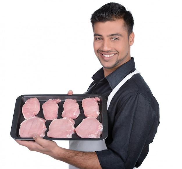 Açougueiro segurando carne vermelha e mostrando o alimento no prato. Foto Premium