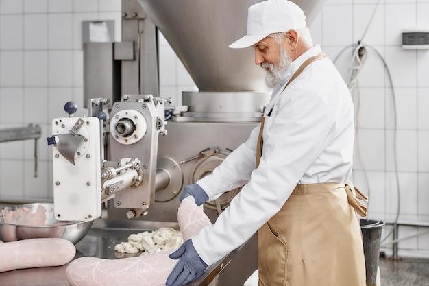 Açougueiro, trabalhando com a produção de salsichas na fábrica. Foto Premium