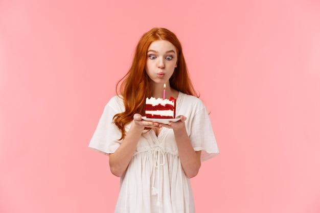 Acredite em milagre. ruiva bonita e boba desejosa fazendo desejo no aniversário, soprando velas no bolo de aniversário com expressão focada, se divertindo, festejando e comemorando no círculo familiar Foto Premium