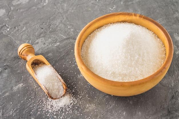 Açúcar de açúcar branco em uma placa de madeira com um dustpan em um fundo escuro. Foto Premium