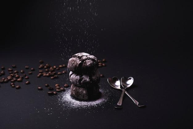 Açúcar de confeiteiro caindo sobre cookies de cacau empilhados com grãos de café torrados e colher em pano de fundo preto Foto gratuita