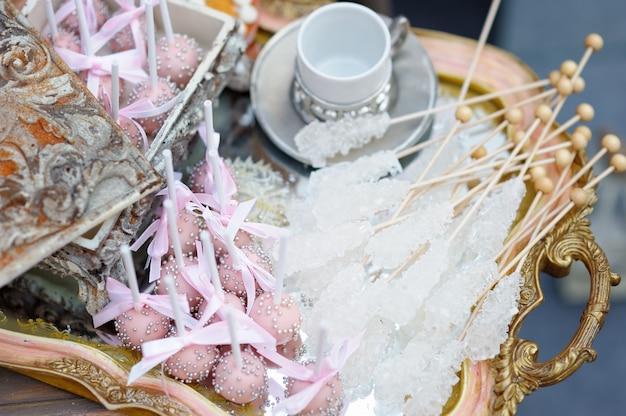 Açúcar em palitos e bolos pop rosa na bandeja de chá Foto Premium