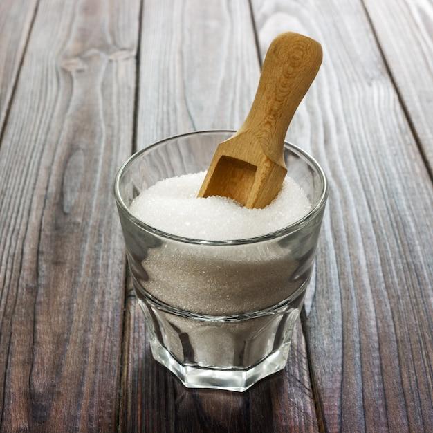 Açúcar granulado branco em copo branco com colher de pau no fundo escuro de madeira Foto Premium