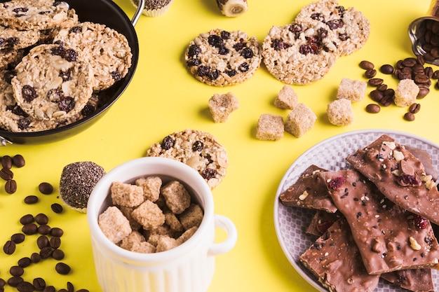 Açúcar mascavo; biscoitos; grãos de café e barra de chocolate no fundo amarelo Foto gratuita