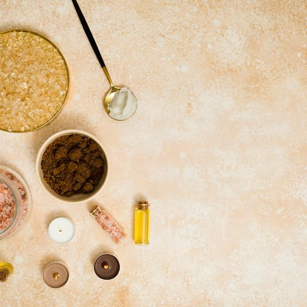 Açúcar mascavo; café em pó; sal rosa himalaia e óleo essencial com velas no pano de fundo texturizado Foto gratuita