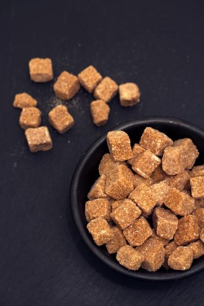 Açúcar mascavo na superfície preta Foto Premium