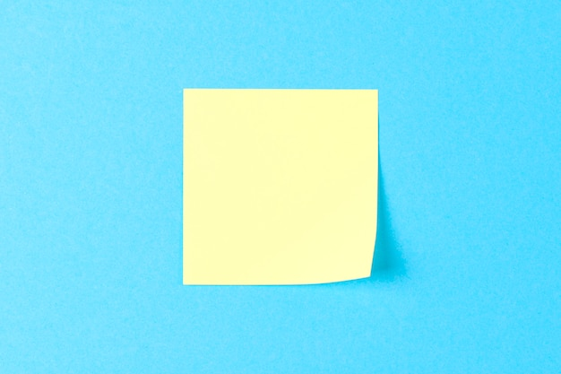 Adesivo amarelo em branco no azul Foto Premium
