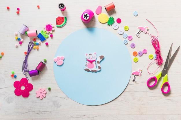 Adesivo de gato e pata no papel circular azul com itens decorativos em plano de fundo texturizado Foto gratuita
