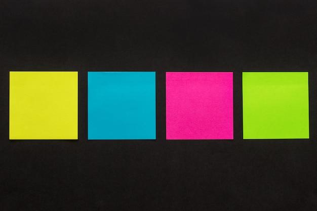 Adesivos coloridos em fundo preto Foto Premium