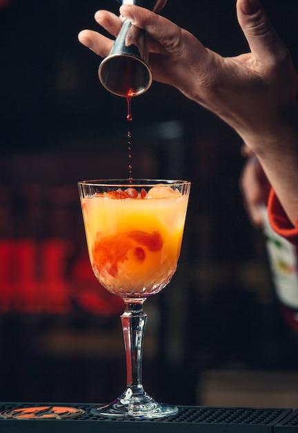Adicionando xarope vermelho no cocktail de laranja. Foto gratuita