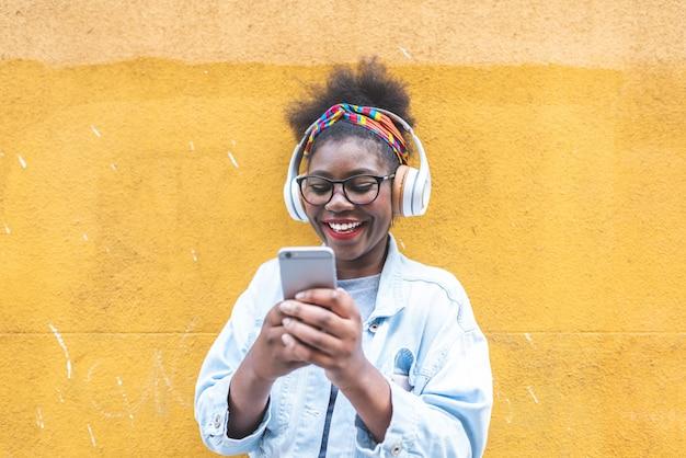 Adolescente afro-americano que usa o telefone celular fora. Foto Premium