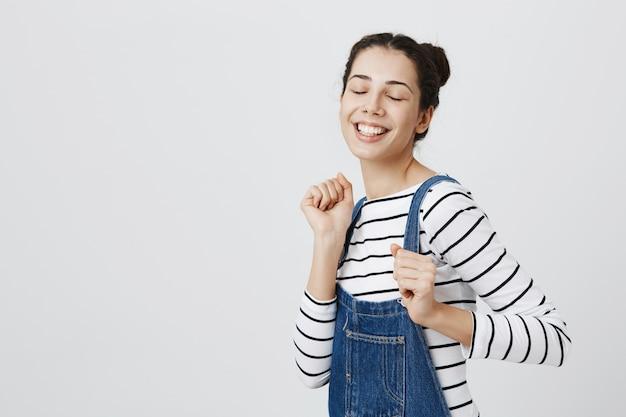 Adolescente alegre dançando com os olhos fechados e sorrindo Foto gratuita