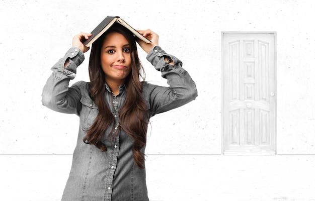 Adolescente alegre que cobre sua cabeça com um livro Foto gratuita