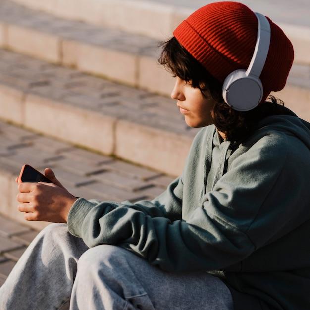 Adolescente ao ar livre usando smartphone e ouvindo música em fones de ouvido Foto gratuita