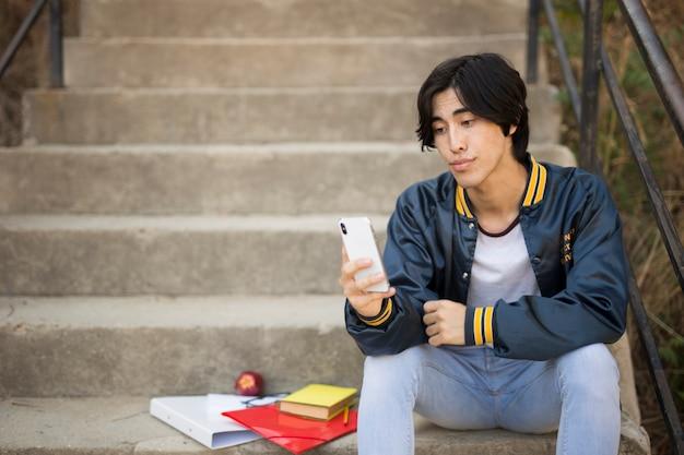 Adolescente asiática sentado com telefone nas escadas Foto gratuita