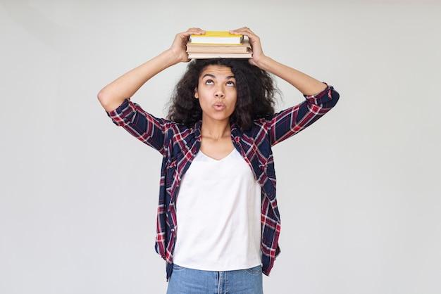 Adolescente brincalhão com livro na cabeça Foto gratuita