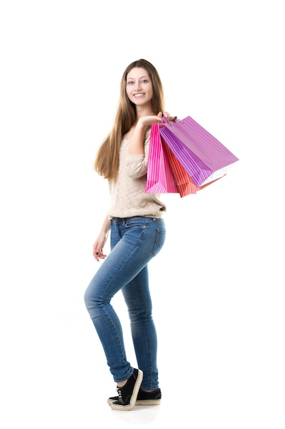 Adolescente com sorriso largo segurando sacos de compras rosa Foto gratuita