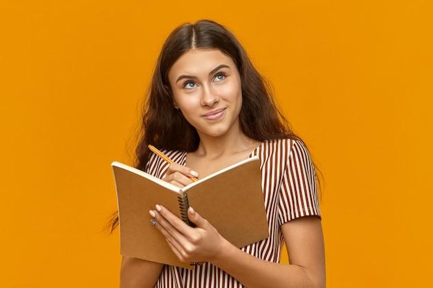 Adolescente criativa vestida com uma blusa listrada segurando o diário e olhando para cima Foto gratuita