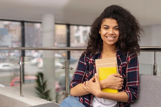 Adolescente de alto ângulo com pilha de livros Foto gratuita