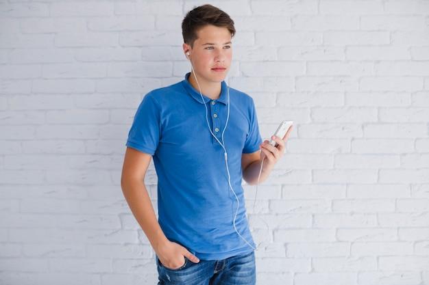 Adolescente de aparência séria ouvindo música Foto gratuita