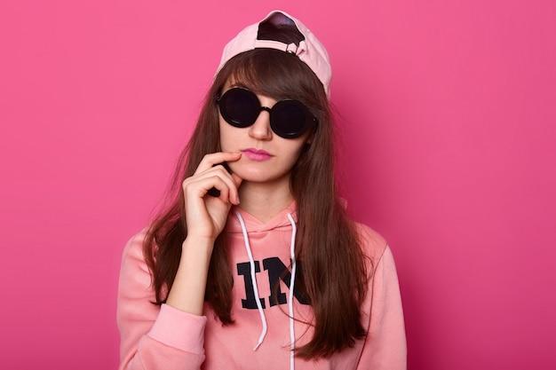 Adolescente de cabelos escuros pensativo, usa roupas elegantes rosa Foto gratuita