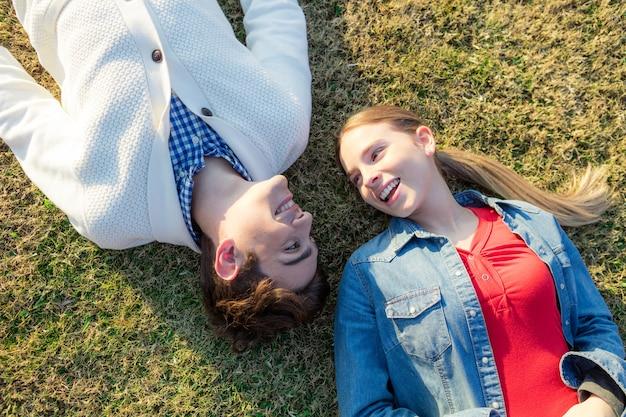 Adolescente deitado na grama com o namorado Foto gratuita
