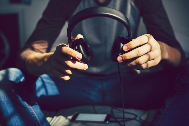 Adolescente em um quarto ouvindo música através de seu smartphone Foto Premium