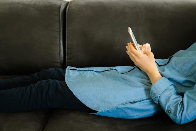 Adolescente em um vestido azul deitada em um sofá enquanto segura um telefone inteligente Foto Premium