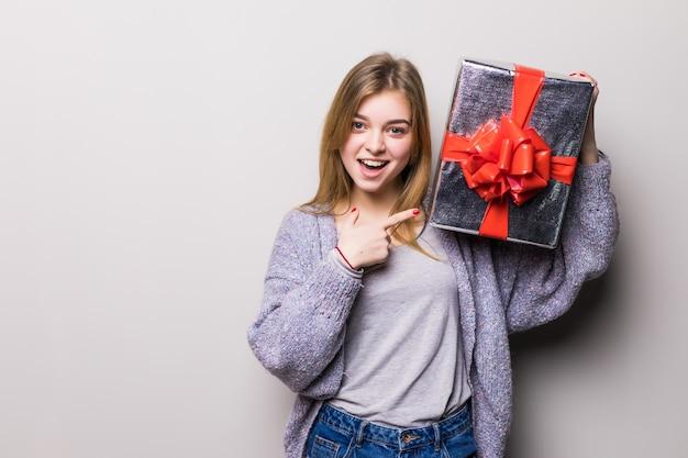 Adolescente encantadora apontando para uma caixa de presente com o dedo isolado no branco Foto gratuita