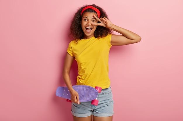 Adolescente engraçada com cabelo encaracolado posando em uma camiseta amarela Foto gratuita